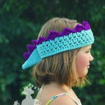 girl wearing crochet dinosaur crown