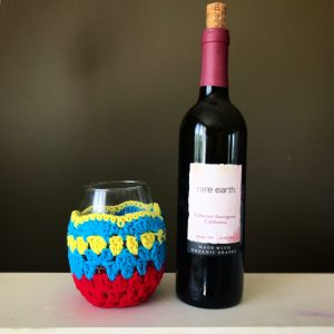 Wineglass with crochet cozy next to wine bottle
