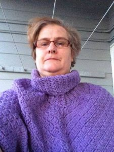 woman wearing glasses and purple crochet poncho