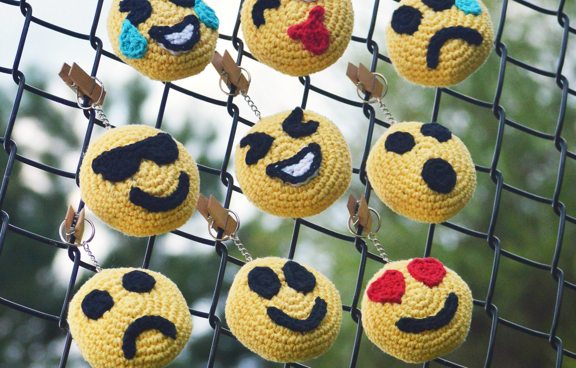 crochet emoji keychain faces on fence