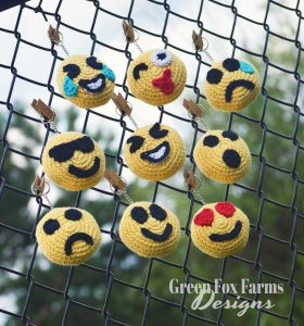 crochet emoji faces on fence