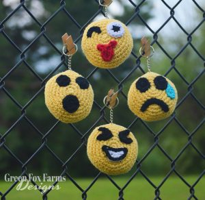 4 crochet emojis on a fence