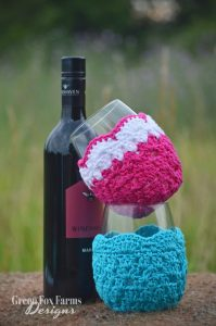 2 stacked glasses with crochet wine glass cozy and bottle of wine