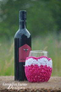 fuchsia crochet wine glass cozy and wine bottle