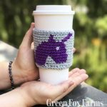 unicorn coffee cozy on cup held in hands