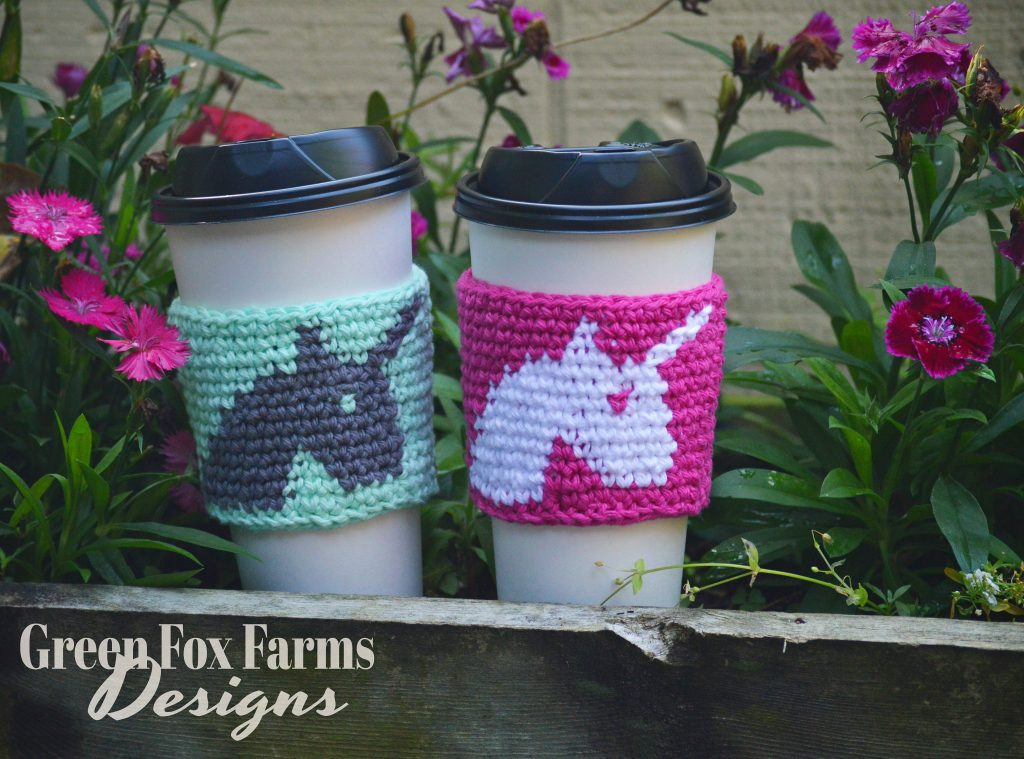 two unicorn coffee cozy on cups with flowers