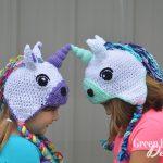 two girls wearing crochet unicorn hats