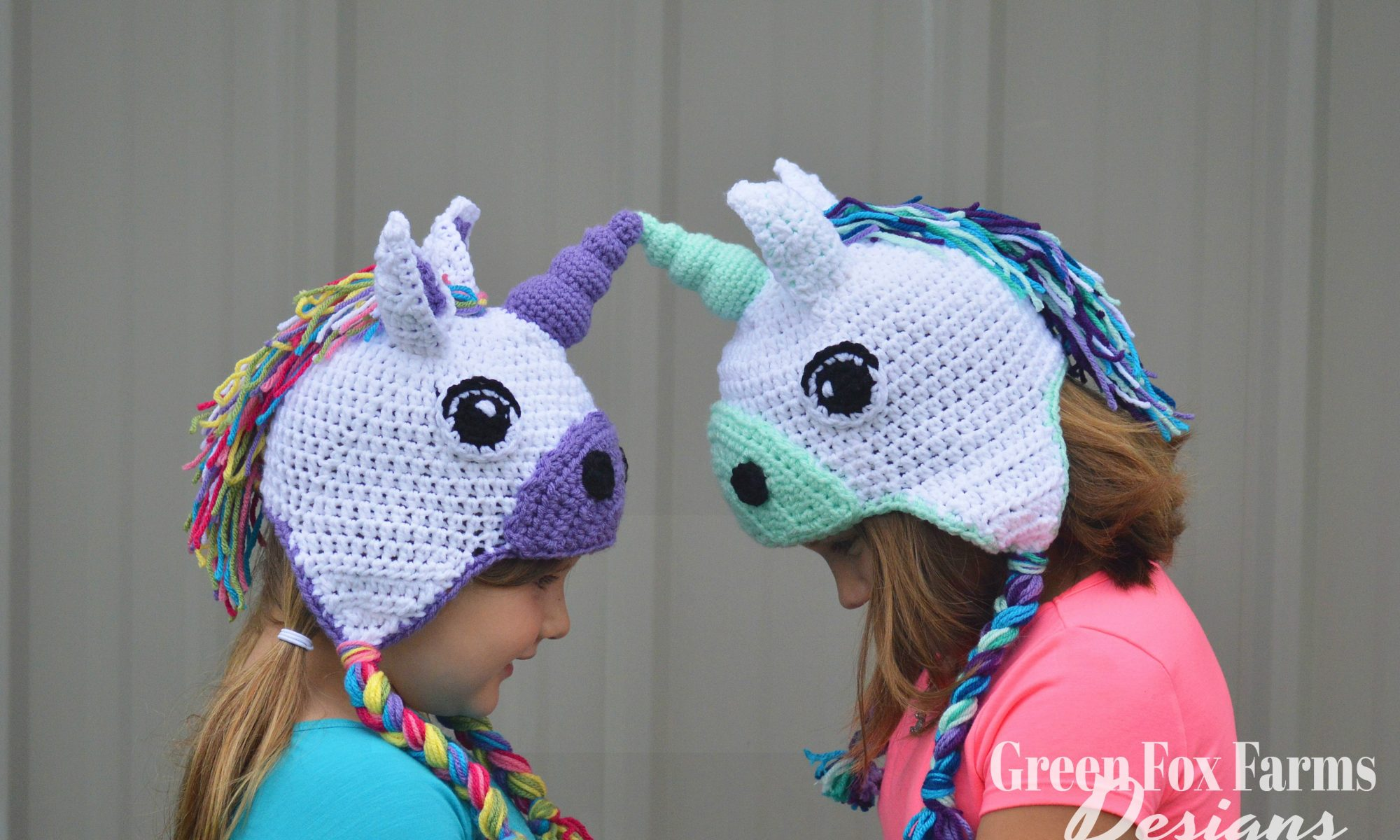 two girls wearing crochet unicorn hats
