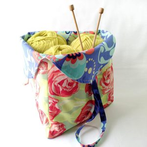 handsewn bag with yarn and needles green and pink floral fabric with blue floral fabric