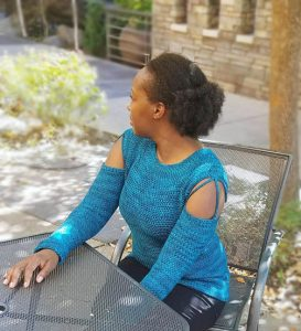 woman sitting at table wearing crochet sweater with open shoulder design