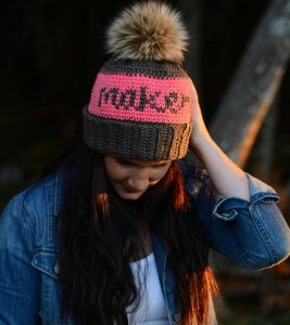 woman wearing crochet maker beanie with fur pom pom