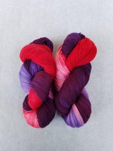 beautiful hand dyed hanks of sock yarn in purples pinks and reds