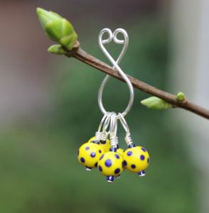 round yellow stitch markers with blue polka dots