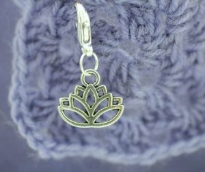 silver lotus flower stitch marker on crochet granny square