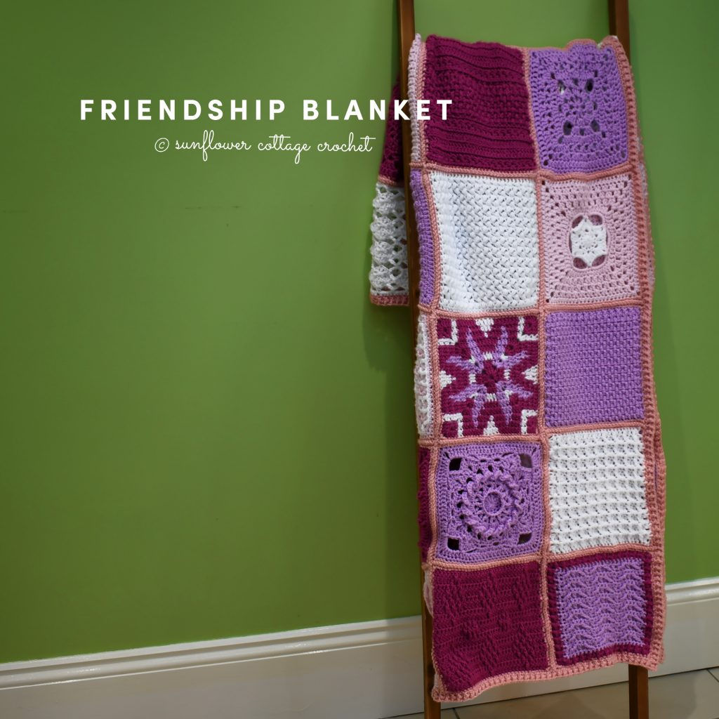 Friendship Blanket hanging from ladder in shades of purple, red, white, and pink by www.suflowercottagecrochet.com